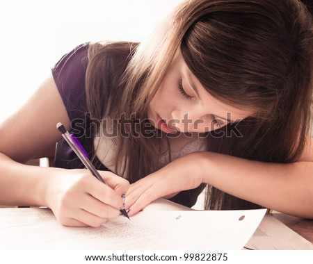 Teenage girl doing homework for school.  This is image is high key. - stock photo