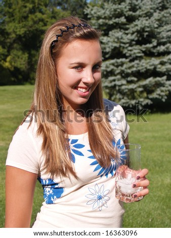 teenage girl drinking water from a glass