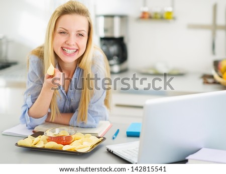 Teenage girl eating chips while studying in kitchen