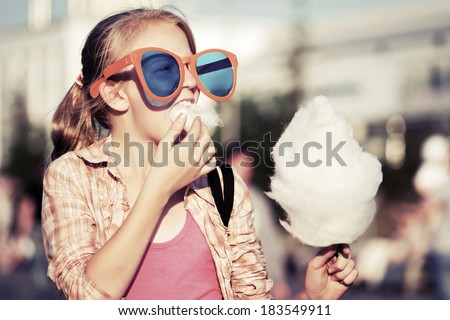 Teenage girl eating cotton candy outdoor - stock photo