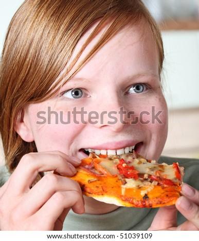 Teenage girl eating pizza - stock photo