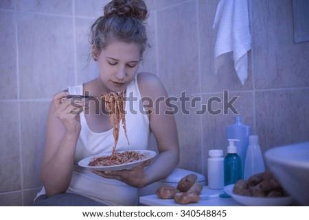 Teenage girl eating spaghetti in bathroom - stock photo