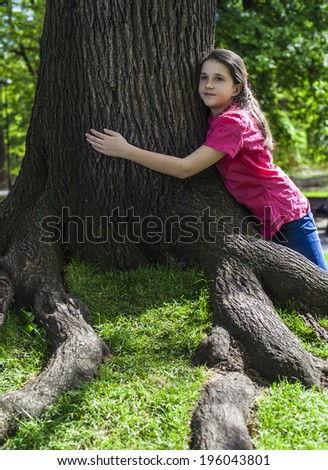 Teenage girl embracing  stem of a tree - stock photo
