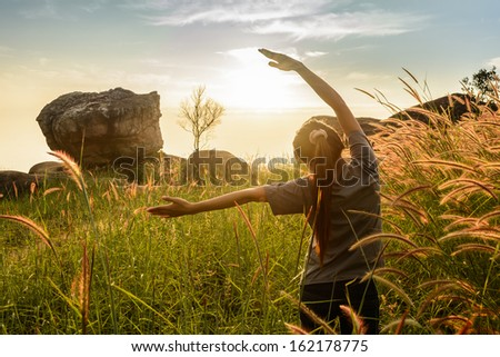 Teenage girl enjoy with sunshine in wheat field - stock photo
