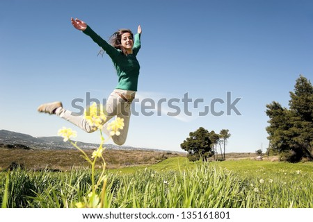 Teenage girl enjoying springtime in the field - stock photo