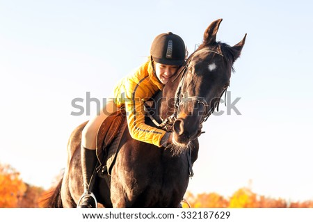 Teenage girl equestrian hugging her lovely horse. Vibrant summertime outdoors horizontal image with filter. - stock photo
