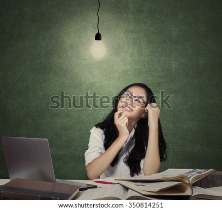 Teenage girl finding idea under bright light bulb while studying with textbooks and laptop - stock photo