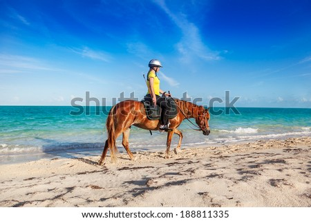 Teenage girl finishing a ride on Long Bay Beach, Providenciales, Turks and Caicos - stock photo