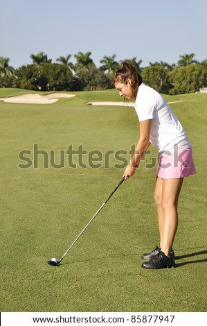 Teenage girl getting ready to drive a golf ball on a golf course in Naples, Florida - stock photo