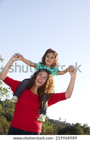 Teenage Girl Giving Toddler a Shoulder Ride Outside with Copy Space