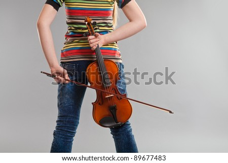 Teenage girl golding violin and bow behind her back - stock photo