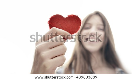 Teenage girl holding a heart of paper and having fun - symbol for love  - stock photo