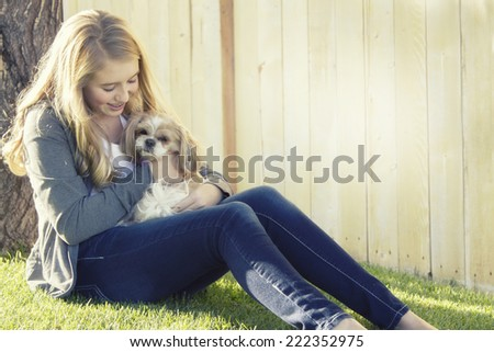 Teenage girl holding a small dog in an outdoor setting