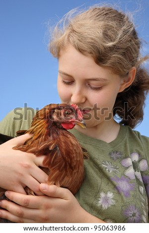 teenage girl holding and loving a pet hen chicken - stock photo