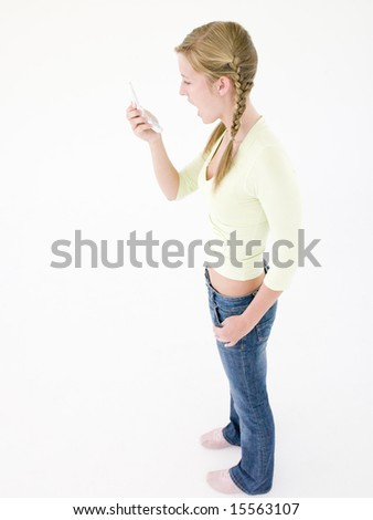 Teenage girl holding cellular phone and smiling - stock photo