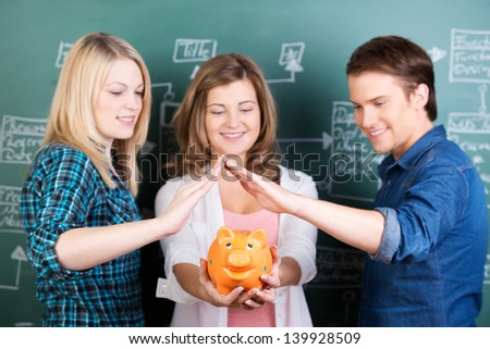 Teenage girl holding piggybank while friends protecting it against chalkboard in classroom - stock photo