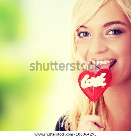 Teenage girl holding red heart shaped lollipop  - stock photo