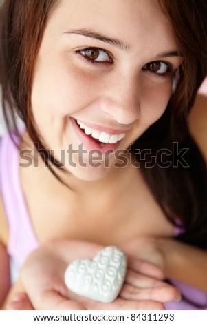 Teenage girl holding silver heart - stock photo