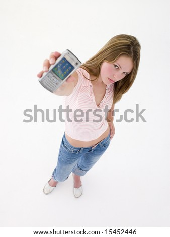 Teenage girl holding up cellular phone and frowning - stock photo