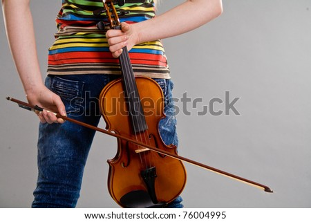 Teenage girl holding violin and bow behind her back - stock photo