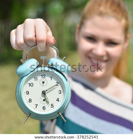 Teenage girl holding vontage clock outdoors with focus on clock - stock photo