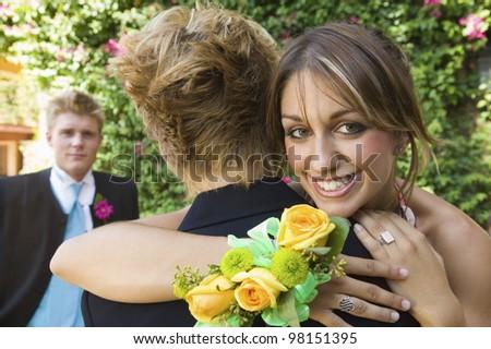 Teenage Girl Hugging Best Friend at School Dance - stock photo