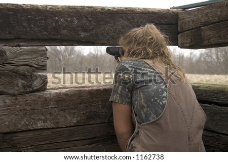 Teenage girl in a blind looking at deer with binoculars - stock photo