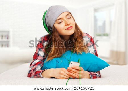 Teenage girl in a checked shirt with a smartphone - stock photo