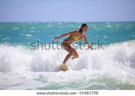 teenage girl in a yellow bikini surfing in Hawaii - stock photo