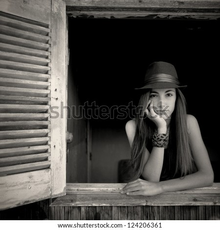 Teenage girl in an open window. A beautiful teenage girl is posing in an open window of a very old house - stock photo