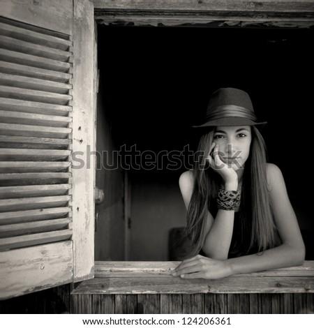 An open window a beautiful teenage girl is posing in an open window