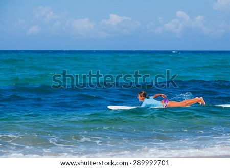 Teenage girl in blue learning to surf