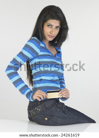 Teenage girl in blue top with credit card - stock photo
