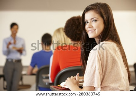 Teenage girl in class smiling to camera - stock photo