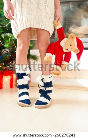 Teenage girl in cozy warm striped woolen blue socks with pompons holding christmas teddy bear toy. Indoors. - stock photo