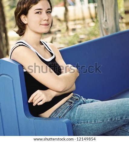 Teenage girl in jeans relaxing outdoors, looking confident and amused.