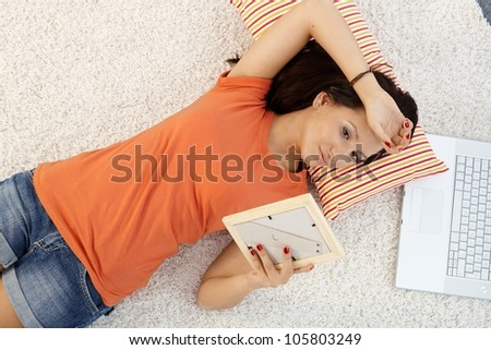 Teenage girl in love daydreaming at home, laying on floor, view from above. - stock photo