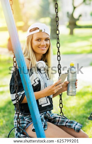 Teenage girl in park in summer sitting on swing, with smart phone, headphones and bottle of water. Sporty young woman relaxing outdoors in summer.