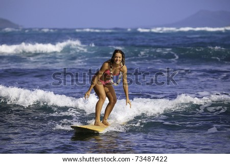 teenage girl in pink bikini surfing in hawaii