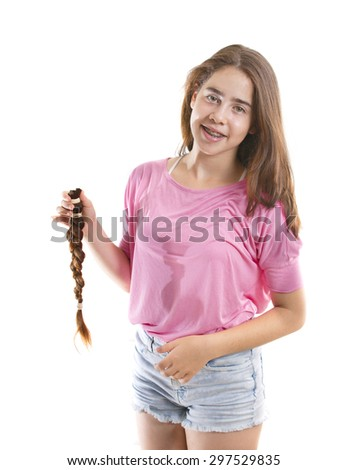 Teenage girl in pink donating her hair to cancer patients - holding her former ponytail after a haircut, generously donating her long hair for making wigs for cancer patients who lost their hair - stock photo
