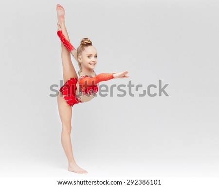 Teenage girl in red dress doing gymnastic exercises on light background. - stock photo