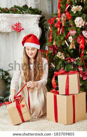 Teenage girl in santa cap sits on furry rug under Christmas tree, untying ribbon  on gift box - stock photo