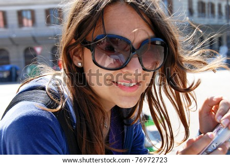 teenage girl in sunglasses with camera smiling outdoor - stock photo