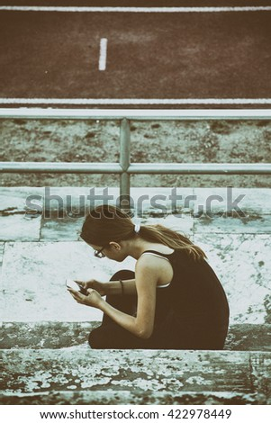 Teenage girl in the city with the smart phone -blue toned - stock photo