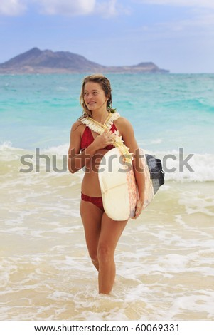 teenage girl in the ocean with her surfboard at kailua beach in Hawaii - stock photo