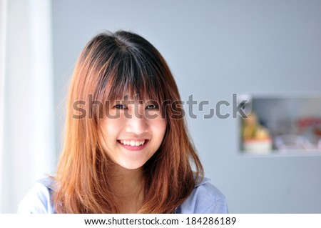 Teenage girl is smiling and happy near the glass door - stock photo