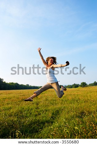 Teenage girl jumping in the air with sky as background. Listening to music on mp3 player. - stock photo