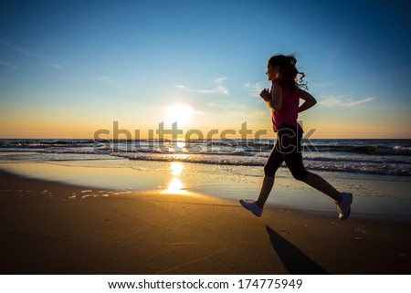 Teenage girl jumping, running on beach  - stock photo