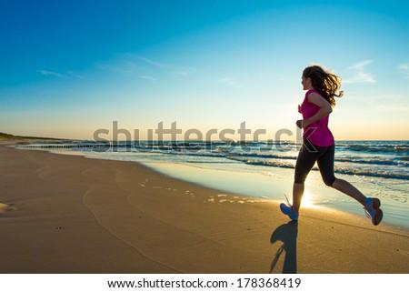 Teenage girl jumping, running on beach  - stock photo