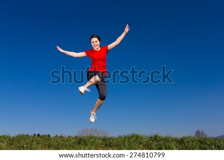 Teenage girl jumping, running outdoor against blue sky  - stock photo